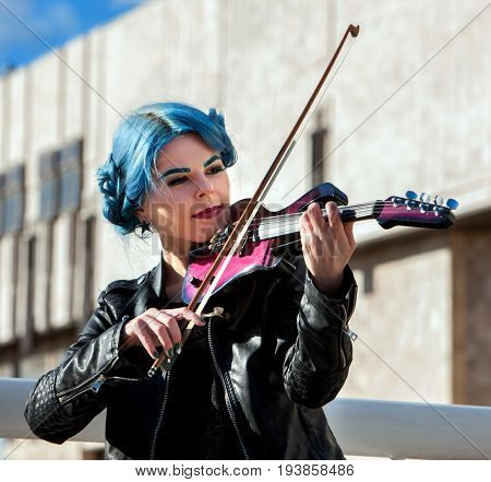 Woman perform music on violin in park outdoor. Girl with blue hairstyle performing jazz on city street . Spring outside city building background. Favorite female hobby.