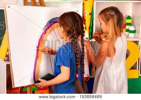 Children painting finger on easel. Group of kids girl and boy with teacher learn paint in class school. Child picture on background. Students draw a rainbow.