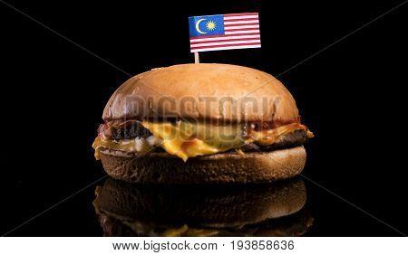 Malaysian Flag On Top Of Hamburger Isolated On Black Background