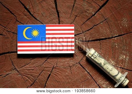 Malaysian Flag On A Stump With Syringe Injecting Money In Flag