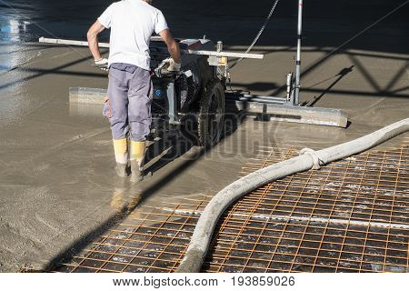 Construction worker with concrete floor laser leveling screed machine