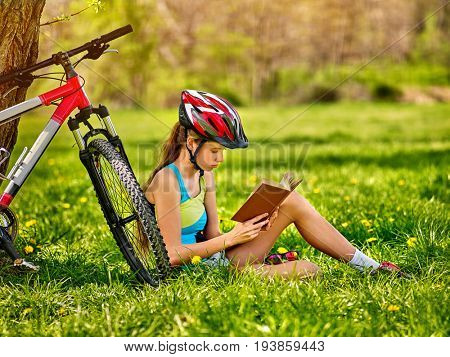 Woman traveling bicycle in summer park. Girl read book on rest near your vehicle. Cycling is good for health. Cyclist is preparing for exam in park. Reading and sport in summer vacation.