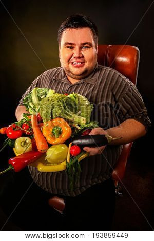 Diet fat man eating healthy food with vegetables cauliflower and sweet pepper with radish, tomatoes for overweight person. Fat man with a hill of fresh vegetables. Abundance of food concept.