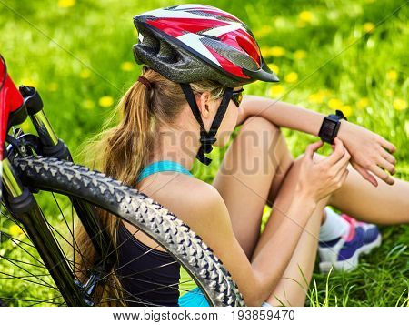 Woman traveling bicycle in summer park. Bicyclist girl watch on smart watch. Girl counts pulse after sport training. Cycling is good for health. Internet and gadget addiction idea.