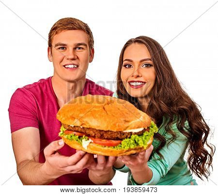Couple eating fast food. Man and woman treat big hamburger with ham. Friends give burder junk on white background isolated. Harm from fast food idea.