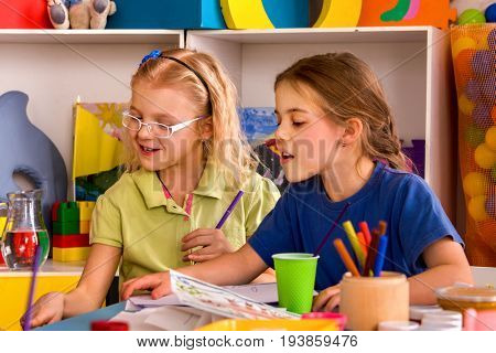Small students girl painting in art school class. Children female drawing by paints on table in kindergarten. Craft drawing education develops creative abilities of children.