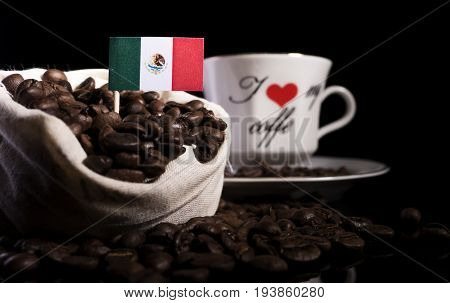 Mexican Flag In A Bag With Coffee Beans Isolated On Black Background