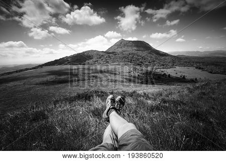 Puy de Dome mountain and hikers legs Auvergne France
