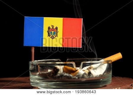 Moldovan Flag With Burning Cigarette In Ashtray Isolated On Black Background