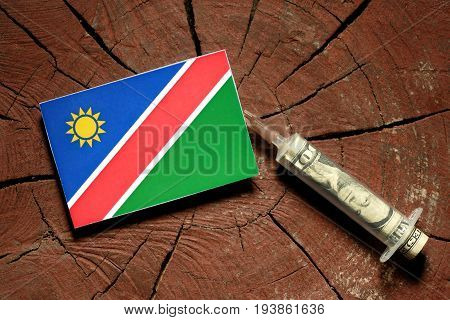 Namibian Flag On A Stump With Syringe Injecting Money In Flag
