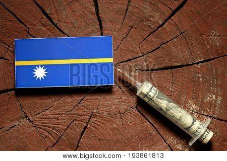 Nauru Flag On A Stump With Syringe Injecting Money In Flag