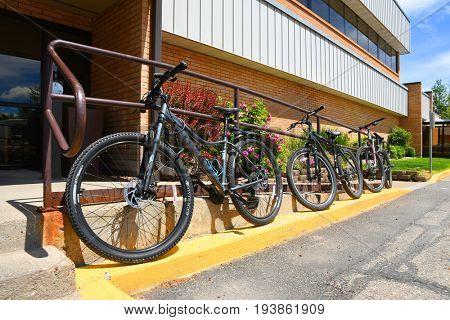 KALISPELL, MONTANA, USA - June 21, 2017: Row of mountain bikes locked onto railing outside an office building