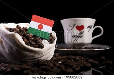Niger Flag In A Bag With Coffee Beans Isolated On Black Background