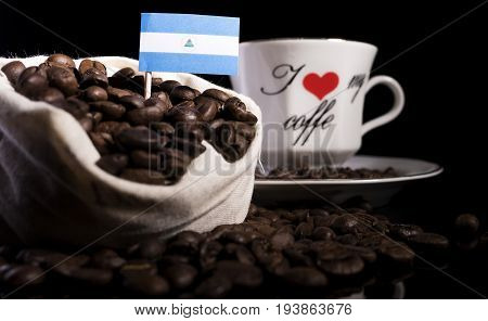 Nicaraguan Flag In A Bag With Coffee Beans Isolated On Black Background