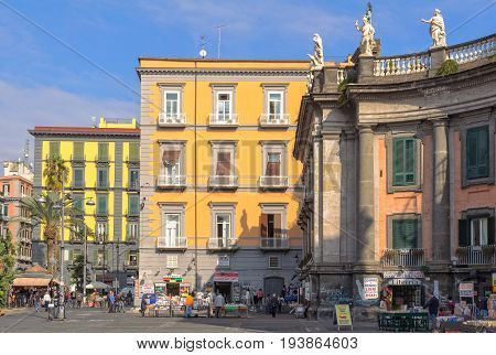 Street vendors and little shops offer their goods in front of colorful buildings in the corner of the Dante Square - Naples, Campania, Italy, 29 October 2011