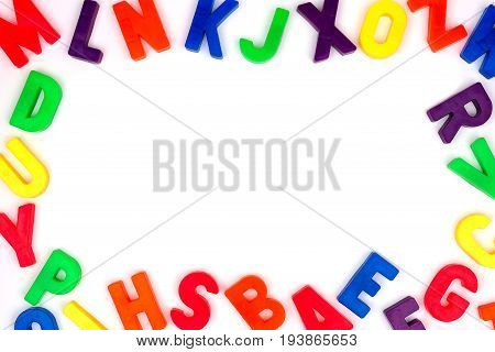 Frame Of Colorful Toy Magnetic Alphabet Letters Over A White Background