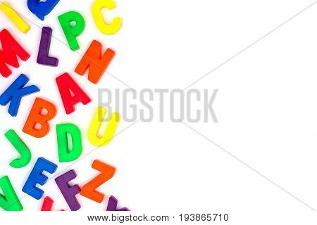 Side Border Of Colorful Toy Magnetic Alphabet Letters Over A White Background