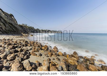 Rocky shore with motion blur waves at secluded Dume Cove in Malibu, California.