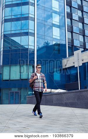 Mid shot of young attractive man with sunglasses walking and listening to the music. Urban life concept