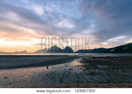 EL NIDO, PALAWAN, PHILIPPINES - MARCH 29, 2017: Wide angle view of sunset with a single boat at Las Cabanas Beach.