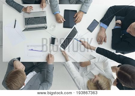 Business people brainstorming at office desk, analyzing financial reports and working with laptops and tablets