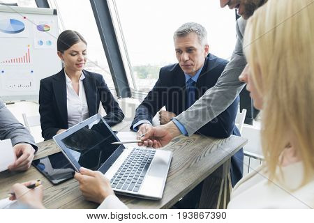 Business people work with laptop and financial statistics in office