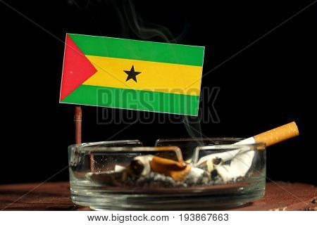 Sao Tome And Principe Flag With Burning Cigarette In Ashtray Isolated On Black Background