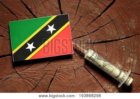 Saint Kitts And Nevis Flag On A Stump With Syringe Injecting Money In Flag
