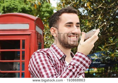 Portrait of young latin man sending voice messages. Outdoors. Urban scene.
