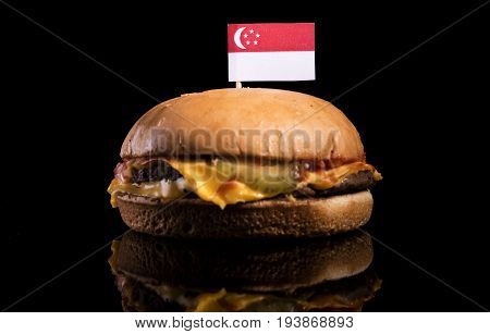 Singaporean Flag On Top Of Hamburger Isolated On Black Background