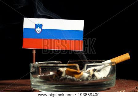 Slovenian Flag With Burning Cigarette In Ashtray Isolated On Black Background