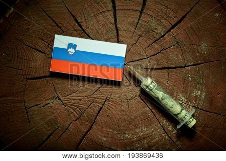 Slovenian Flag On A Stump With Syringe Injecting Money In Flag