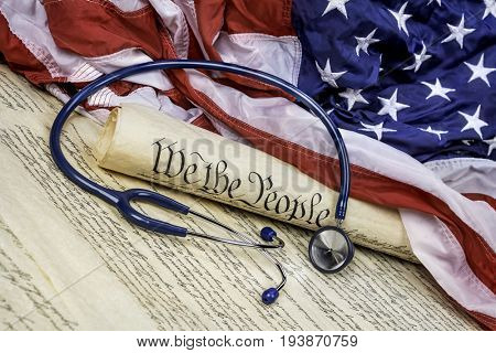 The United States Constitution rolled up on an American flag with a medical stethoscope symbolizing the need for good healthcare