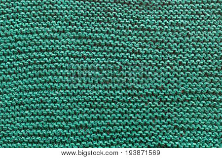 A close-up of a green knitted sweater. Patterns texture