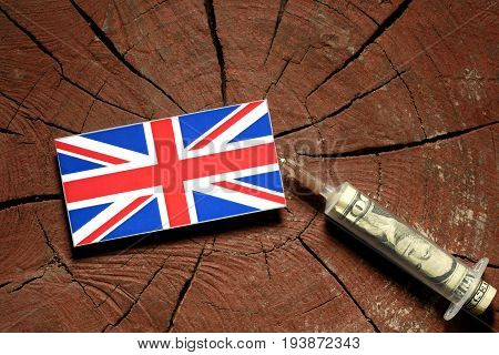 British Flag On A Stump With Syringe Injecting Money In Flag
