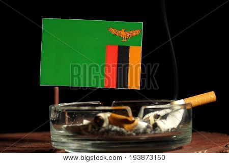 Zambia Flag With Burning Cigarette In Ashtray Isolated On Black Background