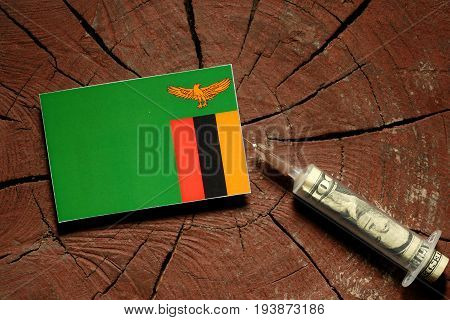 Zambia Flag On A Stump With Syringe Injecting Money In Flag