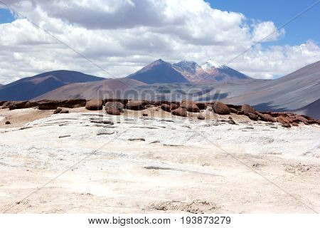 Salt flats red rocks and volcanic mountains of San Pedro de Atacama Chile South America. Colorful landscape with volcanic mountain snow peak.