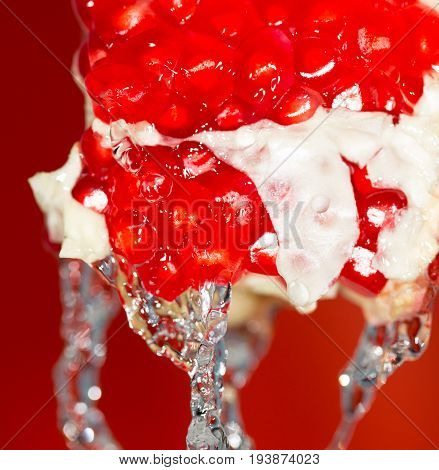 Ripe red pomegranate in water . A photo