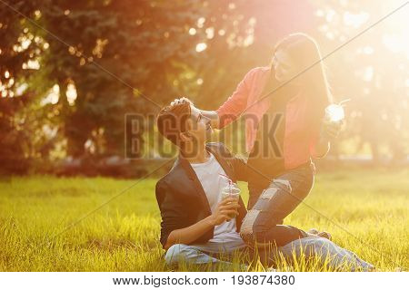 A loving couple of teenagers. Sudden picnic in the park at sunset. Teens drink soft drinks sitting on the lawn. He embraces her. She strokes his head.