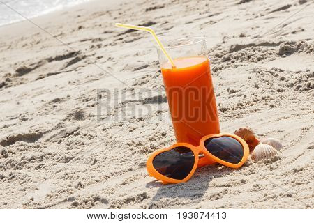 Carrot Juice And Sunglasses At Beach, Concept Of Vitamin A And Beautiful, Lasting Tan