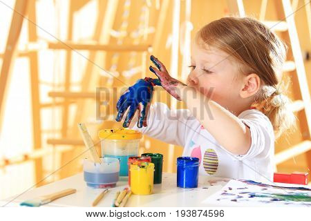 White girl paint hand with blue paint. Close-up of kid paying with paint.  Funny child development background.