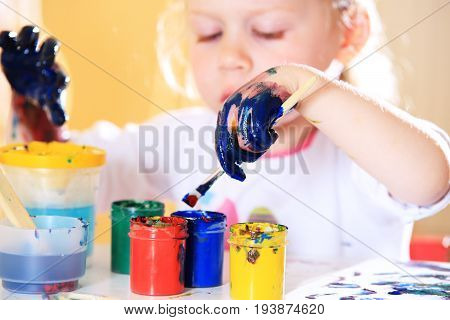 Girl with colorful paints close-up. Kid hands in blue paint. White little girl try draw with brush.