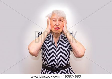 Senior Woman With Head In Hands Looking Weary at studio