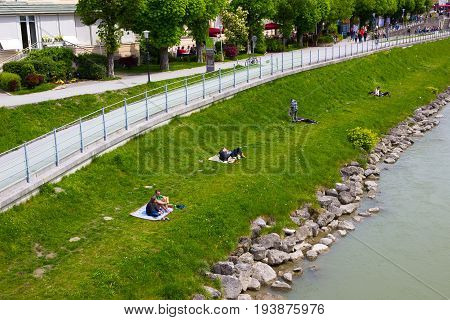 Salzburg, Austria - May 01, 2017: The people resting near Salzach river in summer, Salzburg, Salzburger Land, Austria