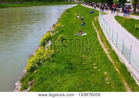 Salzburg, Austria - May 01, 2017: The people resting near Salzach river in summer, Salzburg, Salzburger Land, Austria