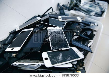 TOMSK, RUSSIA - June 29, 2017: Close-up of used mobile phone batteries, tablets, broken screens LCD iPhone, panels, laptop batteries collected for disposal in plastic packaging in the repair room and greenpeace.