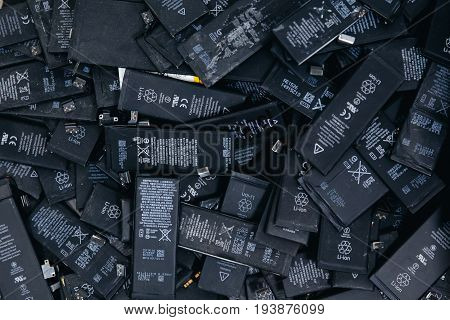 TOMSK, RUSSIA - June 29, 2017: Close-up of used Li-ion mobile phone batteries for recycling, collected in plastic containers.