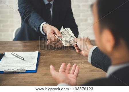 Businessman giving money Japanese Yen to his partner while making contract