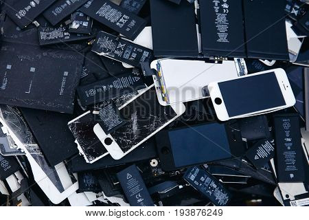 TOMSK, RUSSIA - June 29, 2017: Close-up of used mobile Li-ion phone batteries, broken screens LCD iPhone, panels, laptop batteries collected for disposal in plastic containers.